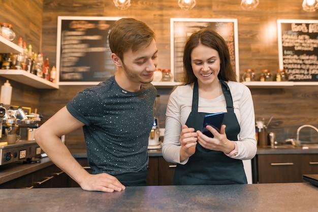 Giovani lavoratori della caffetteria uomo e donna dietro il bancone del bar, parlando esaminando smartphone Foto Premium