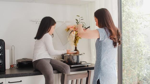 Giovani mamma e figlia giapponesi asiatiche che cucinano a casa. pasta e spaghetti di fabbricazione felici delle donne di stile di vita insieme per il pasto della prima colazione in cucina moderna a casa di mattina. Foto Gratuite