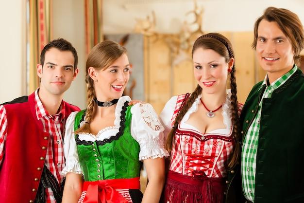 Giovani nel tradizionale bavarese tracht in ristorante o pub Foto Premium