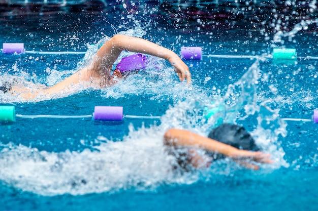 Giovani nuotatori del ragazzo che corrono nello stile libero Foto Premium