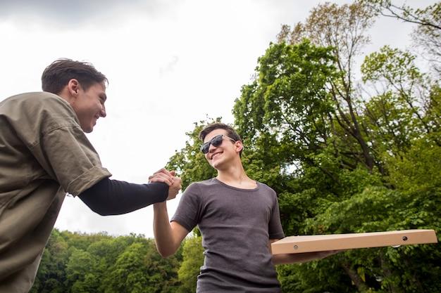 Giovani ragazzi si stringono la mano in natura Foto Gratuite