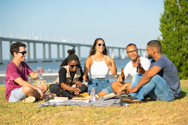 Giovani sorridenti che hanno picnic in parco. amici sorridenti che si siedono sulla coperta e che bevono birra. tempo libero Foto Gratuite