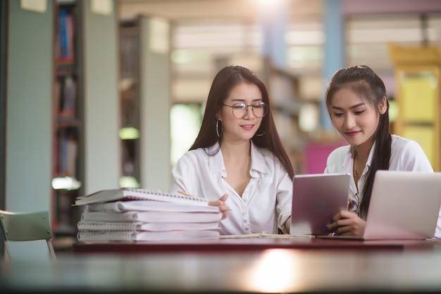 Giovani studenti che imparano, scaffali di biblioteca Foto Gratuite