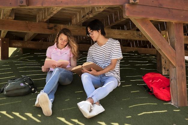 Giovani studenti diversi con blocco note su erba Foto Gratuite