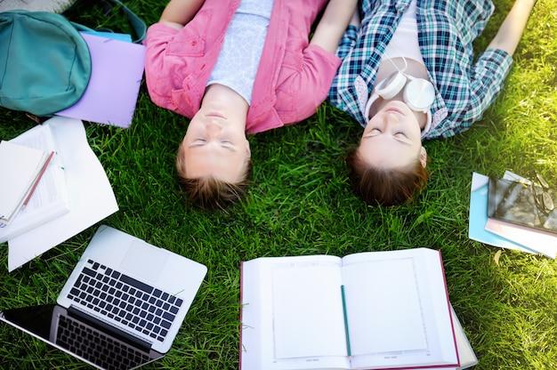 Giovani studenti felici con libri e note all'aperto Foto Premium
