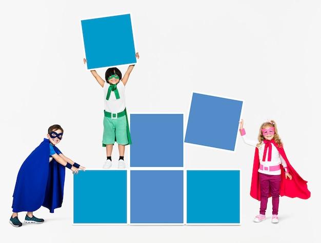 Giovani supereroi che impilano scatole vuote Foto Premium