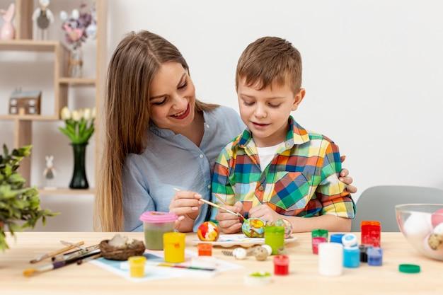 Giovani uova della pittura del figlio e della mamma per pasqua Foto Gratuite