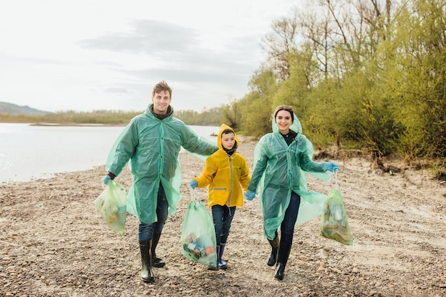 Giovani volontari con sacchetti di immondizia. ecologia. giovane famiglia sulla natura. Foto Premium