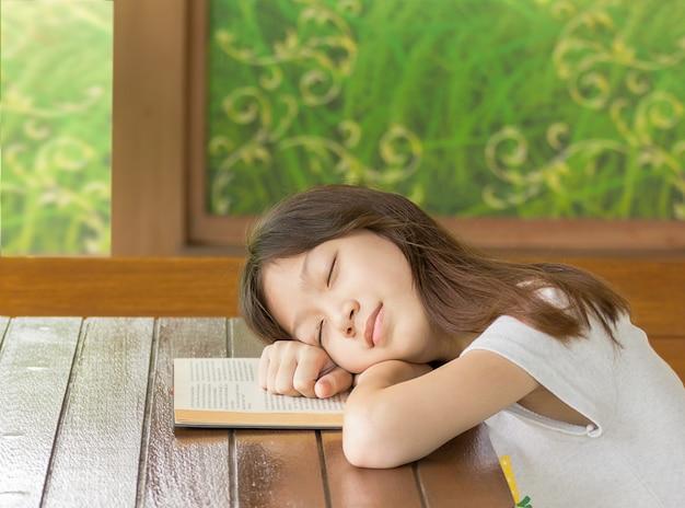 Gir asiatico che dorme mentre impara Foto Premium