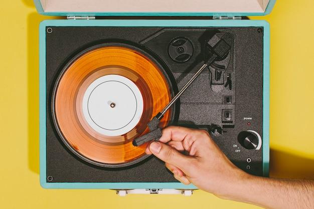 Giradischi vintage con mano e disco in vinile arancione Foto Gratuite