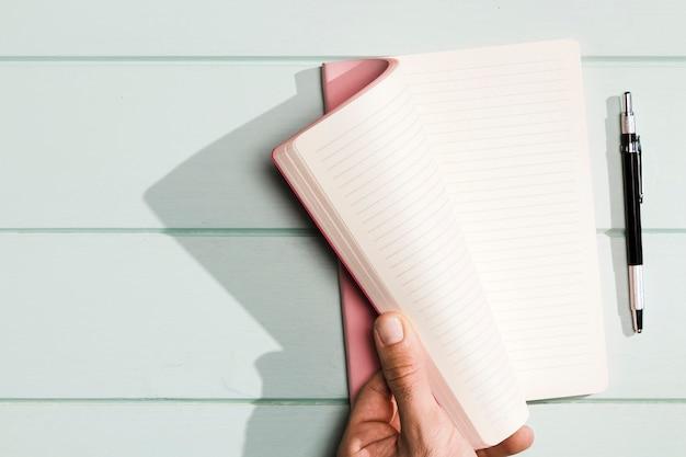 Girando a mano le pagine del quaderno con copertine rosa Foto Gratuite