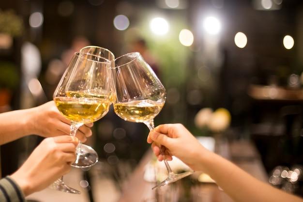 Girato in alto iso con gruppo di luce bassa di amici che brindano al vino Foto Premium