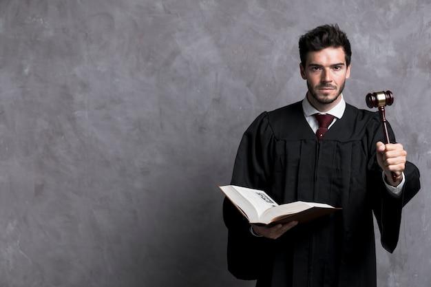 Giudice di tiro medio con libro e martelletto Foto Gratuite