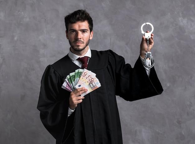 Giudice di vista frontale con manette e banconote Foto Gratuite