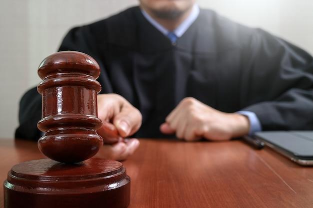 Giudice maschio in un'aula di tribunale che colpisce il martelletto, funzionante con il computer digitale della compressa Foto Premium