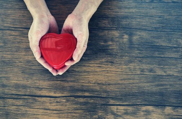 Give love man holding cuore rosso nelle mani per amore san valentino prendersi cura Foto Premium