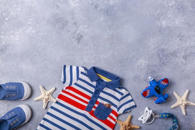 Gli accessori del piccolo bambino o del neonato sulla superficie di gray viaggiano con il concetto del bambino Foto Premium