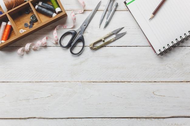 Gli accessori per la parte superiore sono gli accessori di tailor concept. Gli utensili da taglio sono tagliare forbici, bobine di filo, misura di nastro, bottoni e abiti da cucire. Notebook per il testo spazio libero su sfondo rustico di legno. Foto Gratuite