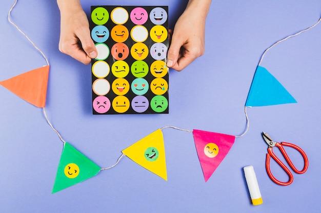 Gli adesivi emoji della tenuta della mano hanno messo vicino a stamina variopinta con le forbici ed il bastone di colla Foto Gratuite