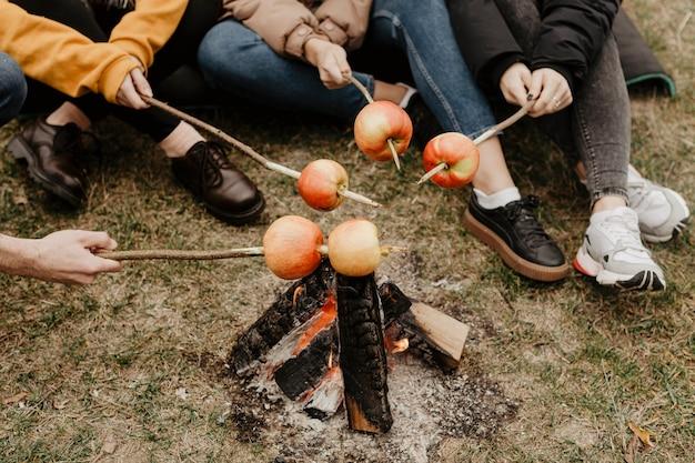 Gli amici che arrostiscono le mele all'aperto si chiudono su Foto Gratuite