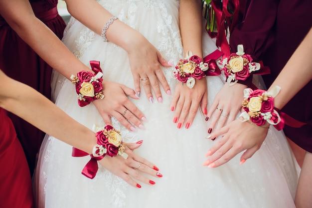 Gli amici della sposa si mostrano l'un l'altro manicure. abiti verdi. concetto di matrimonio, amicizia e moda. le donne sfoggiano la manicure Foto Premium