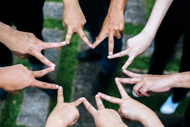 Gli amici di donne e uomini fanno la forma della stella dalle dita. successo, concetto di amicizia. Foto Gratuite