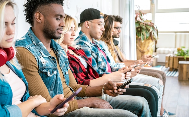 Gli amici multirazziali raggruppano sul momento annoiato usando lo smart phone mobile - fuoco selettivo Foto Premium