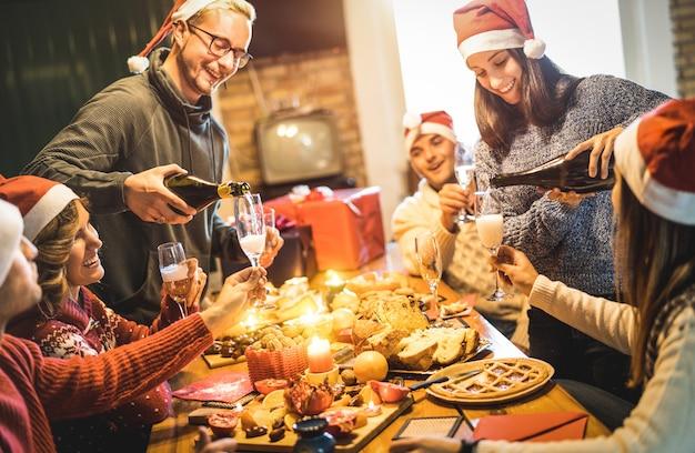Gli amici raggruppano con i cappelli di santa che celebrano il natale con la cena dell'alimento dei dolci e del champagne a casa Foto Premium
