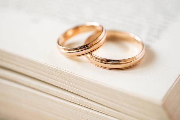 Gli anelli d'oro da matrimonio che si intersecano giacciono sul bordo di un libro aperto. visualizza dall'alto. Foto Premium