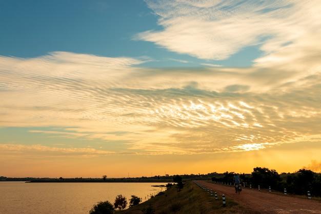 Gli anziani andare in bicicletta sul ciglio della strada del lago, bella nuvola dorata del cielo con il tramonto. bel cielo . Foto Premium