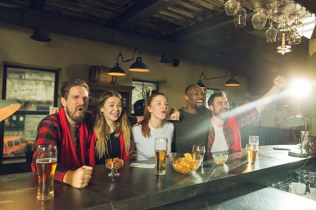 Gli appassionati di sport tifano al bar, pub e bevono birra mentre il campionato, la competizione sta andando Foto Gratuite
