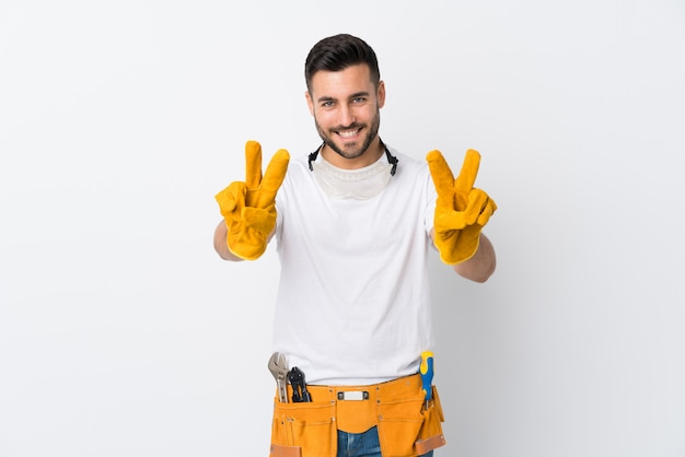 Gli artigiani o l'elettricista equipaggiano la parete bianca isolata che sorride e che mostra il segno di vittoria Foto Premium