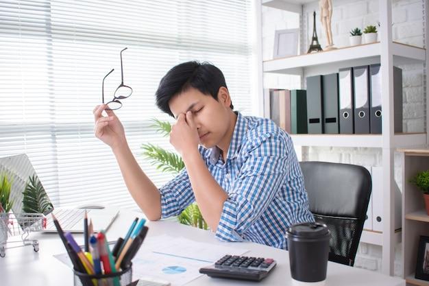 Gli asiatici sono stanchi e usano le mani per coprirsi il viso mentre lavorano in ufficio Foto Premium