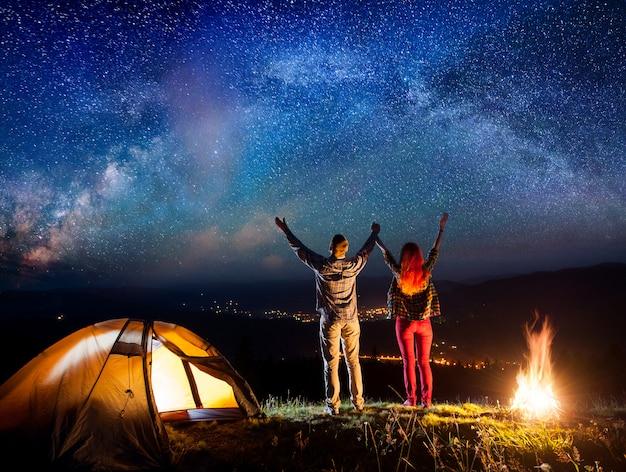 Gli escursionisti alzavano le mani sotto le stelle vicino al fuoco e alla tenda, osservando il cielo stellato di notte Foto Premium