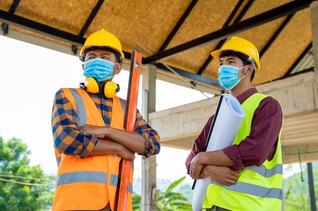 Gli ingegneri del team e i costruttori che indossano maschere protettive per prevenire la polvere e le patologie del 19 durante l'ispezione in cantiere, coronavirus si è trasformato in un'emergenza globale. Foto Premium