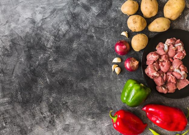 Gli ingredienti per la fabbricazione della carne cruda sul fondo della carta da parati di lerciume strutturano Foto Gratuite