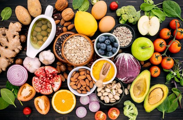 Gli ingredienti per la selezione degli alimenti sani hanno installato su fondo di legno. Foto Premium