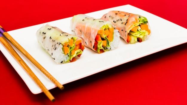 Gli involtini primavera al vapore si dispongono sul piatto bianco con la bacchetta sulla superficie rossa Foto Gratuite