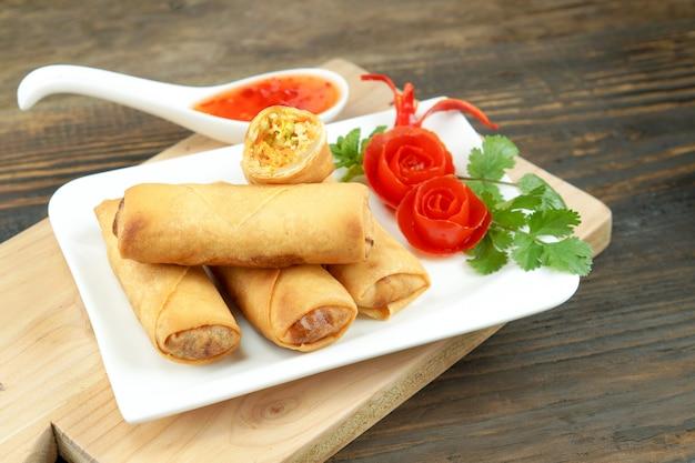 Gli involtini primavera fritti cinesi sono serviti con salsa di peperoncino e pomodori rosa decorati con foglie verdi su legno, spazio. concetto di cibo asiatico Foto Premium