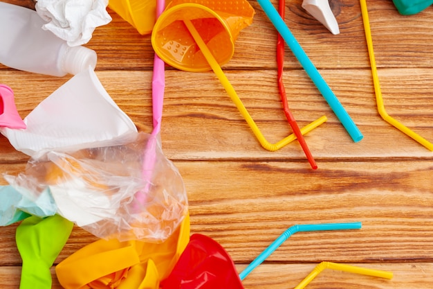 Gli oggetti di plastica, riciclano l'immondizia su una tavola di legno, vista superiore Foto Premium