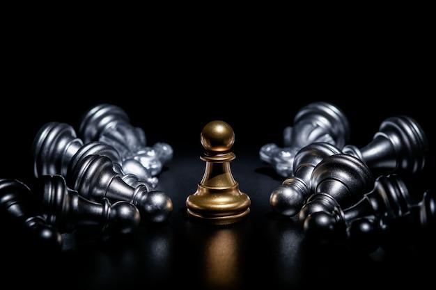Gli scacchi del pegno dell'oro circondati da un certo numero di pezzi degli scacchi d'argento caduti, concetto di strategia aziendale Foto Premium