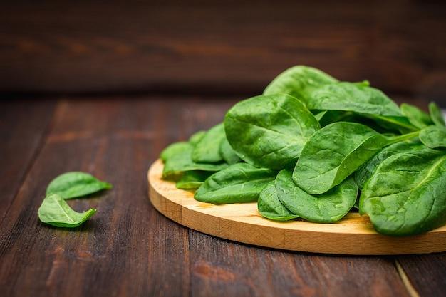 Gli spinaci succosi freschi va su una tavola marrone di legno. prodotti naturali, verdure, cibo sano Foto Premium