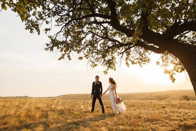 Gli sposi camminano al tramonto. Foto Premium