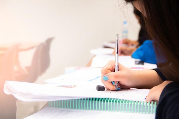 Gli studenti universitari fanno quiz, test o studi dell'insegnante in una grande aula. studenti in uniforme che frequentano la scuola educativa per esame. Foto Premium