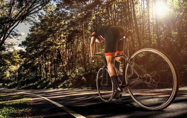 Gli uomini asiatici stanno pedalando in bici al mattino Foto Premium