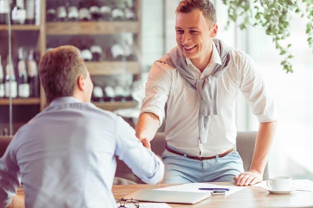Gli uomini d'affari belli si incontrano per lavorare al ristorante Foto Premium