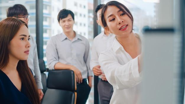 Gli uomini d'affari e le donne di affari dell'asia che incontrano le idee di brainstorming che conducono i colleghi di progetto di presentazione di affari che lavorano insieme progettano la strategia di successo godono del lavoro di squadra in piccolo ufficio moderno. Foto Gratuite