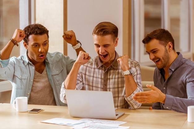 Gli uomini d'affari fanno il tifo e usano il laptop mentre lavorano. Foto Premium