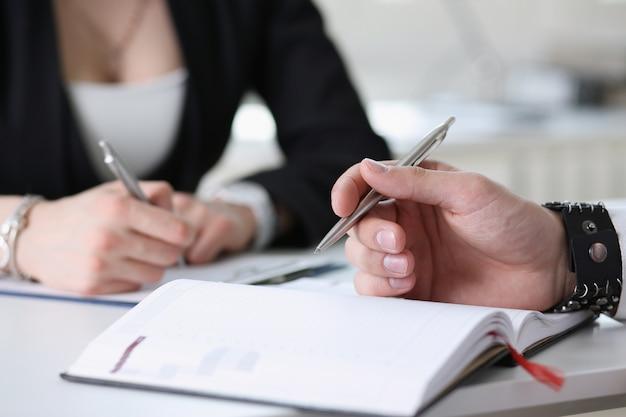 Gli uomini d'affari prendono appunti nel blocco note Foto Premium
