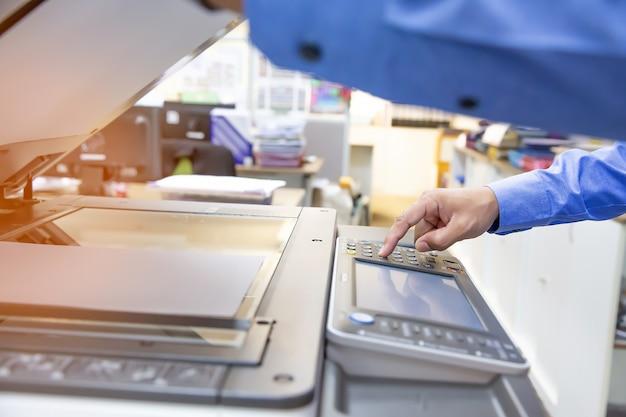 Gli uomini d'affari utilizzano fotocopiatrici, scansionano documenti in ufficio. Foto Premium